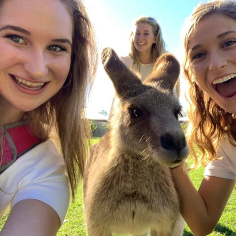Autumn Brown and a friend pose with a small kangaroo while studying in Australia with HIEP in 2019